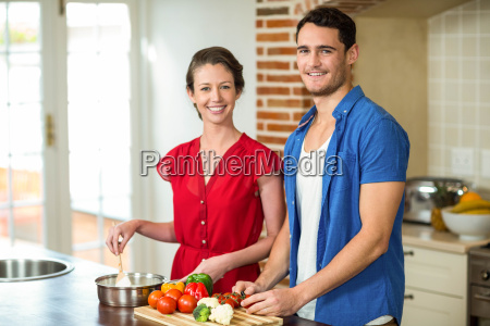 young couple working together in kitchen