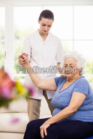 physiotherapist taking care of sick elderly