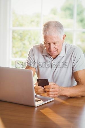 focused elderly man using smartphone and