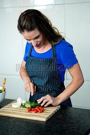 smiling woman preparing vegetables for dinner