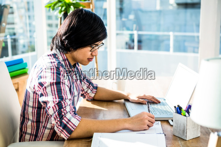 hipster businessman writing while using laptop