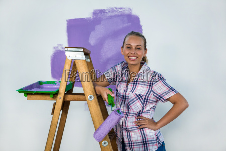 smiling woman painting a wall