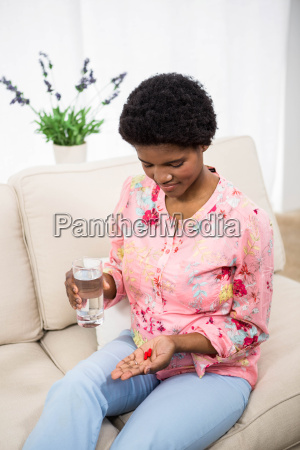 pregnant woman holding pills and glass
