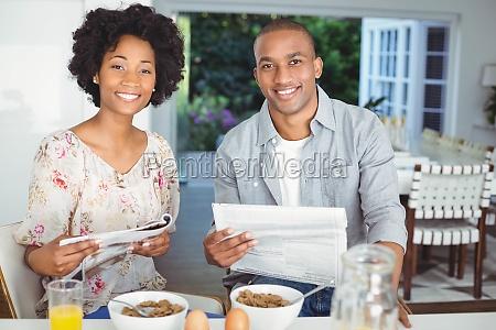 smiling couple reading magazine and documents