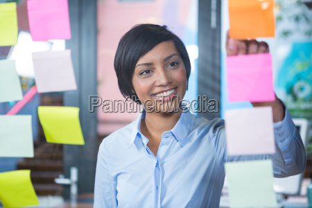 smiling businesswoman looking at sticky note