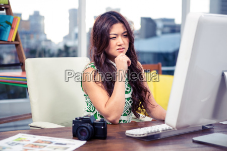 focused asian woman using computer with