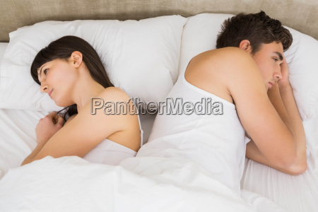 couple sleeping back to back after
