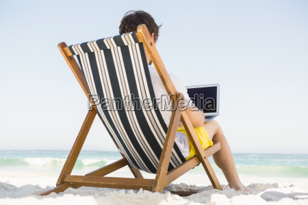 man relaxing and using laptop
