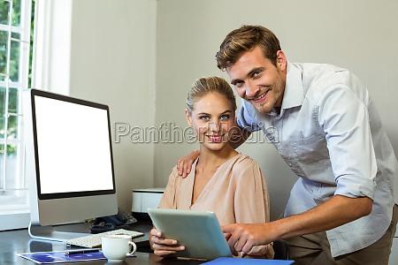 portrait of happy colleagues using digital