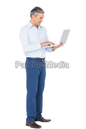 smiling businessman typing on laptop