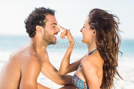 happy girlfriend putting suncream on boyfriend
