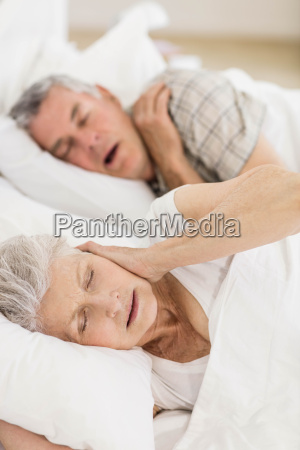 awake senior woman in bed covering