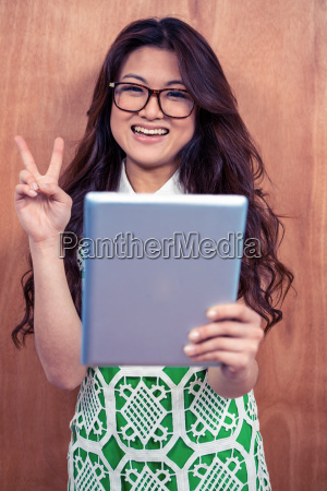 smiling asian woman holding tablet and