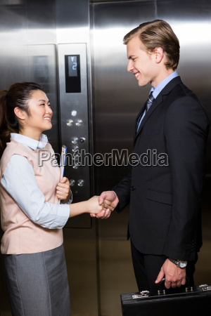 businessman shaking hands with businesswoman in