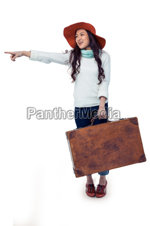 smiling asian woman holding luggage pointing