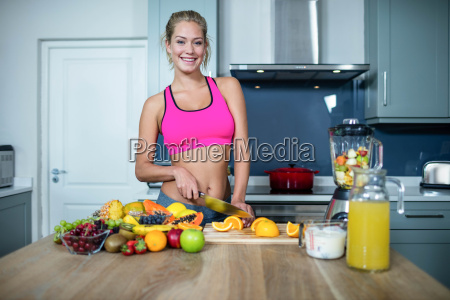 fit woman cutting fruits
