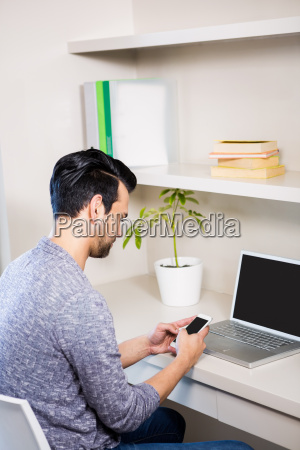 thoughtful man using smartphone and laptop
