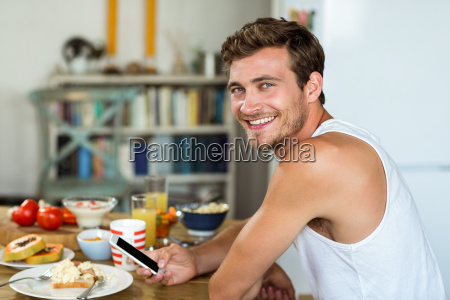smiling young man using mobile phone