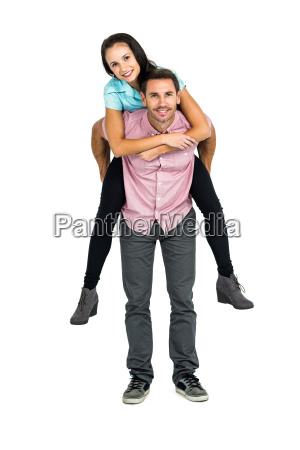 smiling man giving piggy back to