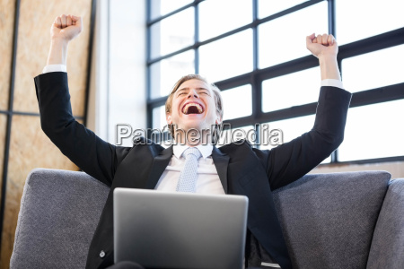 businessman raising hands with excitement in