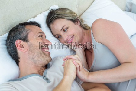 expecting couple lying on bed and