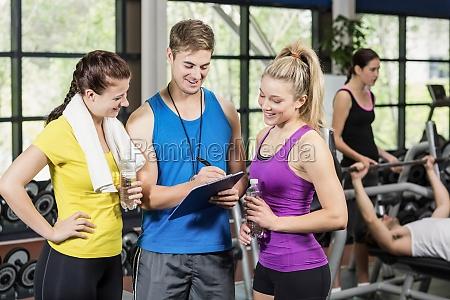 trainer man talking with sportswomen