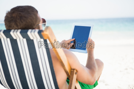 man relaxing and using tablet