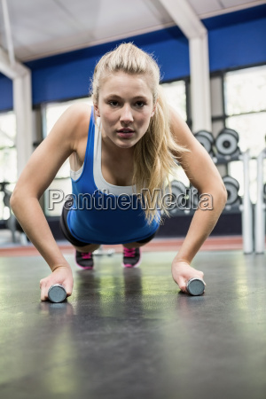 determined woman doing push ups