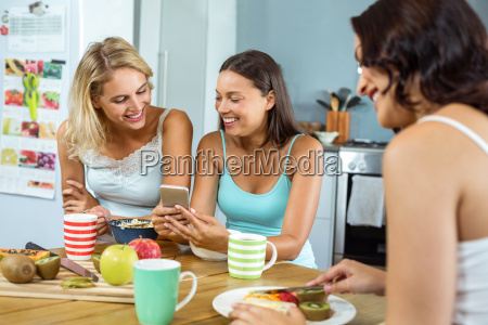 women using mobile phone while friend