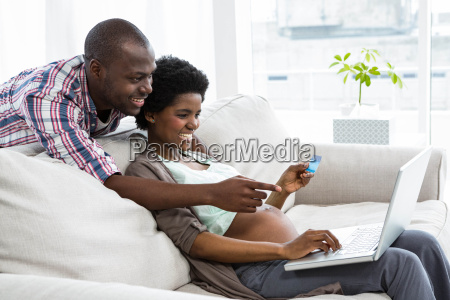 pregnant couple shopping online on laptop