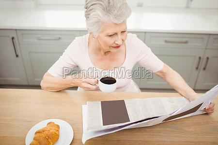 senior woman reading a newspaper