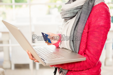 woman using laptop and holding credit