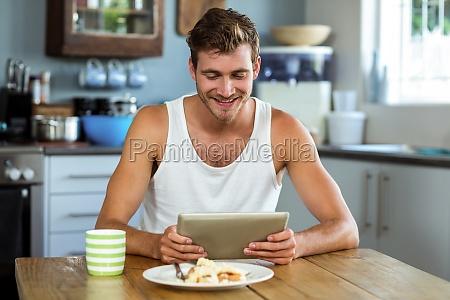 smiling man using digital tablet at
