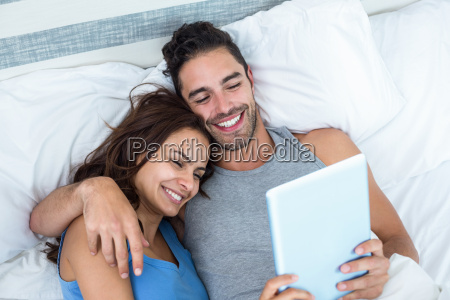 young couple using tablet while lying
