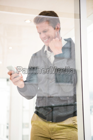 man smiling while using mobile phone