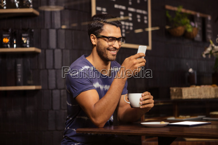 man using his smartphone and drinking