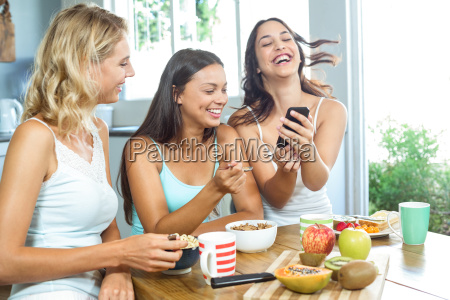 friends having breakfast while using mobile