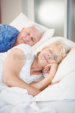 smiling senior woman sleeping besides husband