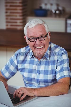 portrait of happy retired man using