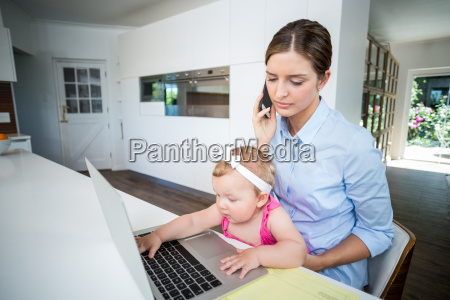woman using mobile phone and baby
