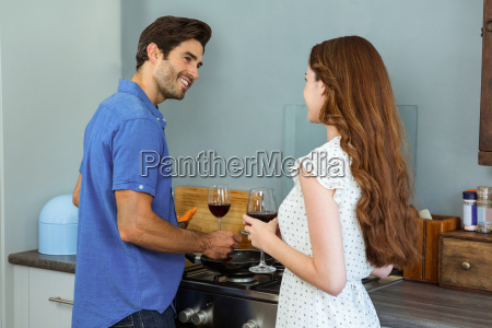 young couple holding wine glass in