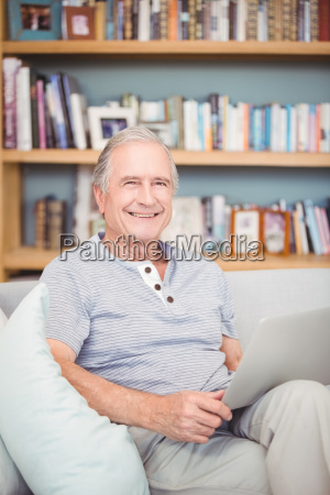 portrait of happy senior man using