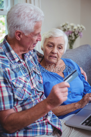 senior couple using credit card and