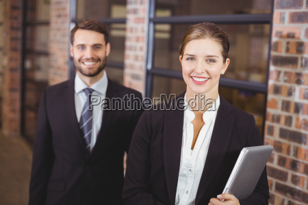 happy businesswoman standing with male colleague