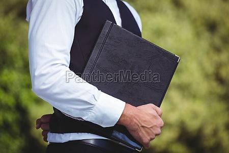 handsome waiter holding menus