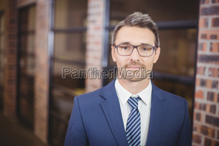 confident businessman standing in office