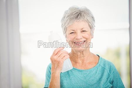 portrait of smiling woman holding bottle