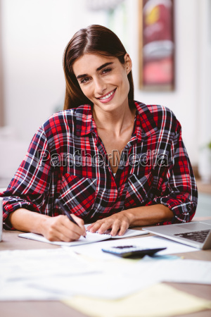 portrait of smiling woman writing in