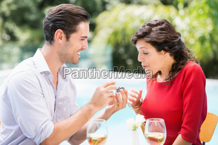 young man giving engagement ring to