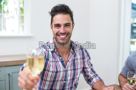 handsome young man showing wineglass while